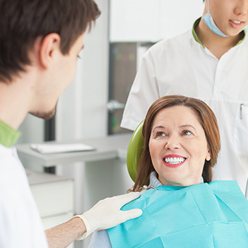 Older woman in dental chair smiling at dentist
