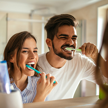 Man and woman brushing teeth together
