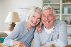 elderly couple smiling with dental implants