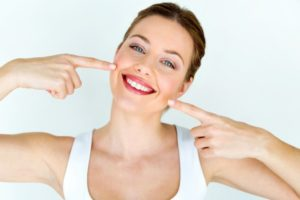 woman smiling and pointing at her teeth