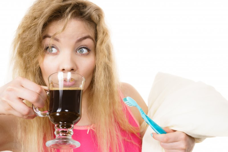 a woman drinking coffee while holding a toothbrush and a pillow